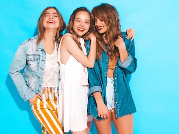 トレンディな夏のカジュアルドレスの3人の若い美しい笑顔の女の子。セクシーな屈託のない女性がポーズします。ポジティブモデル