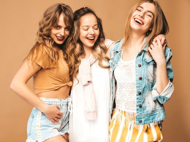 トレンディな夏のカジュアルな服装で3人の若い美しい笑顔の女の子。セクシーな屈託のない女性がポーズします。ポジティブモデル