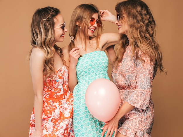 夏のドレスを着た3人の笑顔の美しい女性。ポーズの女の子。カラフルな風船のモデル。楽しんで、お祝いの誕生日や休日のパーティーの準備ができて