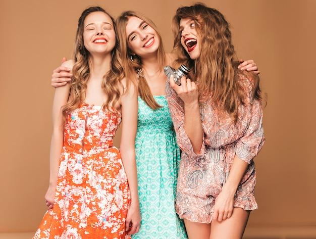 トレンディな夏のカジュアルドレスの3人の若い美しい笑顔の女の子。セクシーな屈託のない女性がポーズします。レトロなカメラで写真を撮る