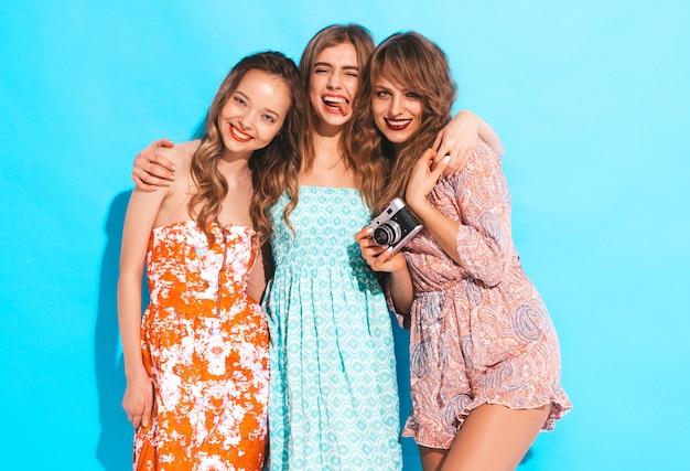 トレンディな夏のカジュアルドレスの3人の若い美しい笑顔の女の子。セクシーな屈託のない女性がポーズします。レトロなカメラで写真を撮る。舌を見せます