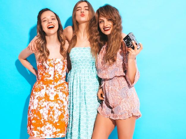 トレンディな夏のカラフルなドレスの3人の若い美しい笑顔の女の子。セクシーな屈託のない女性がポーズします。レトロなカメラで写真を撮る