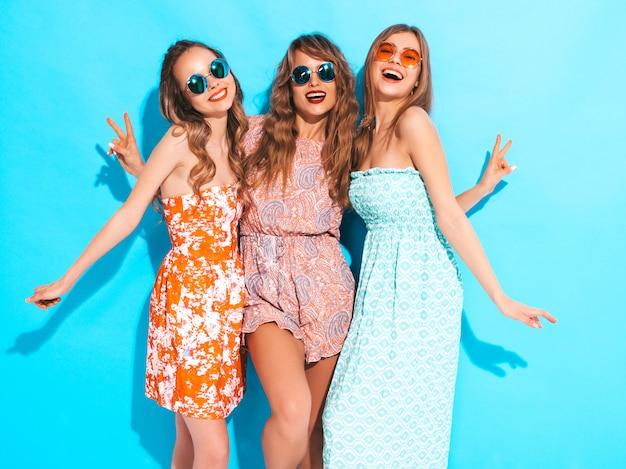 トレンディな夏のカジュアルドレスとサングラスの3人の若い美しい笑顔の女の子。セクシーな屈託のない女性がポーズします。