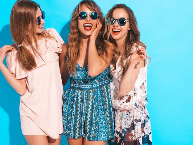 トレンディな夏のカジュアルドレスの3人の若い美しい笑顔の女の子。セクシーな屈託のない女性がポーズします。