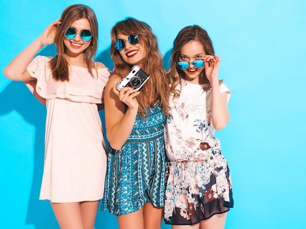 トレンディな夏のカジュアルドレスの3人の若い美しい笑顔の女の子。丸いサングラスでポーズをとってセクシーな屈託のない女性。レトロなカメラで写真を撮る