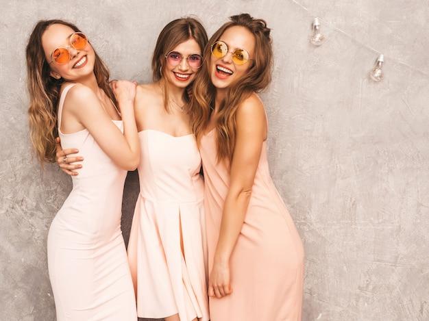 トレンディな夏の3人の若い美しい笑顔の女の子はピンクのドレスを光します。セクシーな屈託のない女性がポーズします。楽しいラウンドサングラスの肯定的なモデル