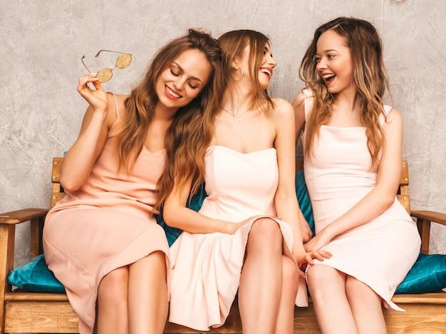 トレンディな夏のピンクのドレスで3人の若い美しい笑顔の女の子。豪華なインテリアのソファーに座っているセクシーな屈託のない女性。楽しくコミュニケーションできるラウンドサングラスのポジティブモデル