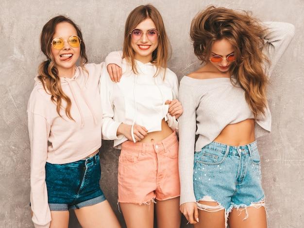 トレンディな夏の3人の若い美しい笑顔の女の子は服をスポーツします。セクシーな屈託のない女性がポーズします。楽しいラウンドサングラスの肯定的なモデル。ハグ