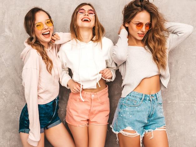 トレンディな夏の3人の若い美しい笑顔の女の子は服をスポーツします。セクシーな屈託のない女性がポーズします。楽しいラウンドサングラスの肯定的なモデル
