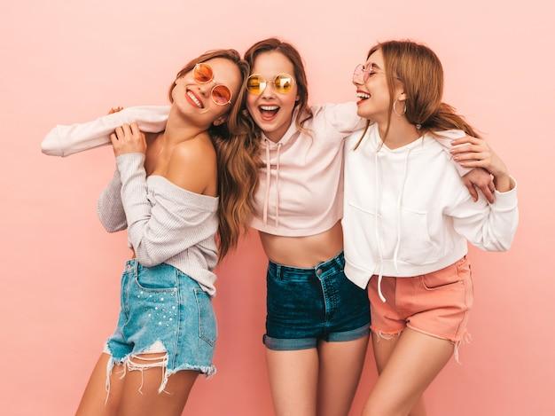 トレンディな夏服で3人の若い美しい笑顔の女の子。セクシーな屈託のない女性がポーズします。楽しいポジティブモデル