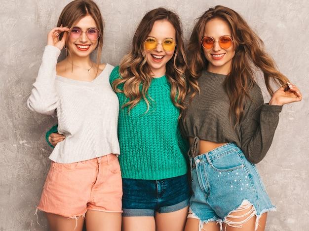 トレンディな夏服の3人の若い美しい笑顔の豪華な女の子。セクシーな屈託のない女性がポーズします。ラウンドサングラスを楽しんでいる肯定的なモデル