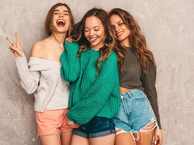 トレンディな夏服の3人の若い美しい笑顔の豪華な女の子。セクシーな屈託のない女性がポーズします。楽しいポジティブモデル