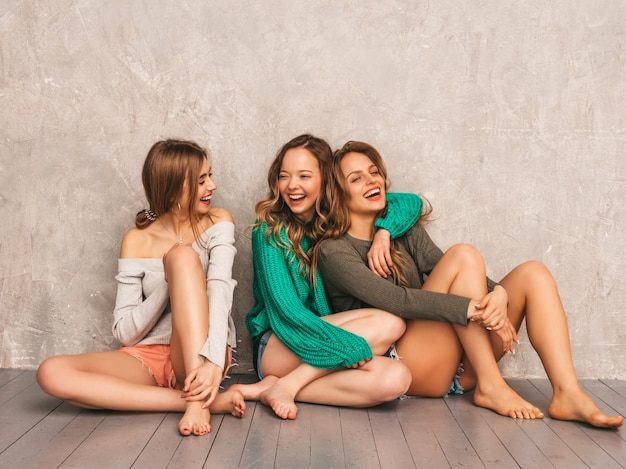 トレンディな夏服の3人の若い美しい笑顔の豪華な女の子。セクシーな屈託のない女性がポーズします。楽しいポジティブモデル。床に座って