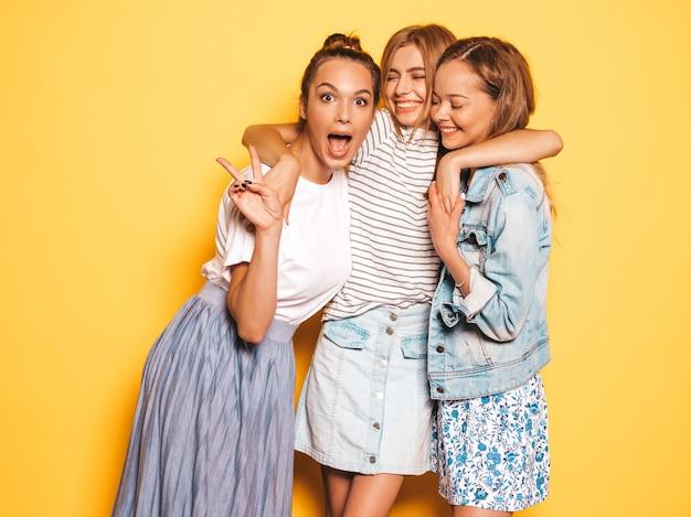 トレンディな夏服で3人の若い美しい笑顔流行に敏感な女の子。黄色の壁に近いポーズセクシーな屈託のない女性。楽しいポジティブモデル