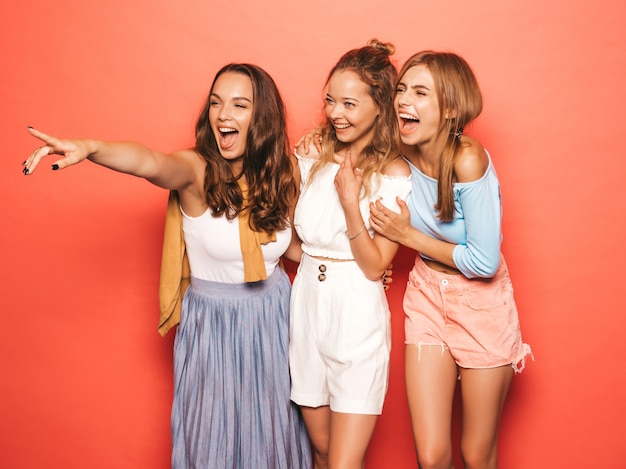 トレンディな夏服で3人の若い美しい笑顔流行に敏感な女の子。ピンクの壁に近いポーズセクシーな屈託のない女性。楽しんでいるポジティブなモデル。