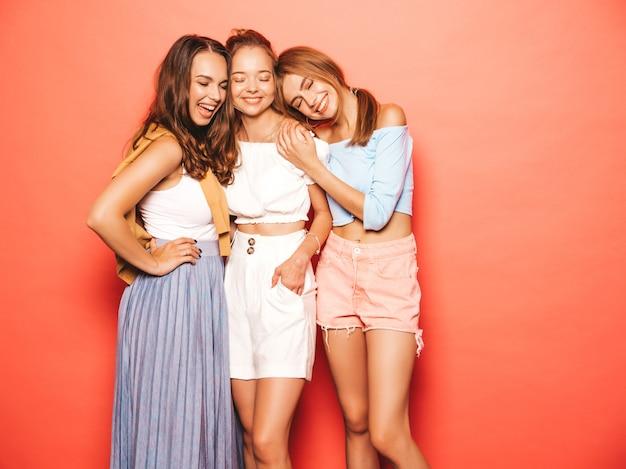 トレンディな夏服で3人の若い美しい笑顔流行に敏感な女の子。ピンクの壁に近いポーズセクシーな屈託のない女性。楽しいポジティブモデル