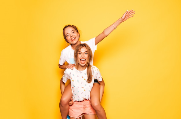 トレンディな夏服で3人の若い美しい笑顔流行に敏感な女の子。黄色の壁に近いポーズセクシーな屈託のない女性。ポジティブなモデルが夢中になって楽しんでいます。サングラスで