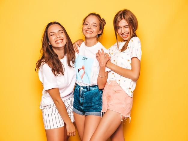 トレンディな夏服で3人の若い美しい笑顔流行に敏感な女の子。黄色の壁に近いポーズセクシーな屈託のない女性。ポジティブなモデルが夢中になって楽しんでいる