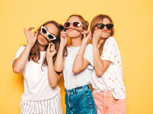 トレンディな夏服で3人の若い美しい笑顔流行に敏感な女の子。黄色の壁に近いポーズセクシーな屈託のない女性。ポジティブなモデルが夢中になって楽しんでいる。