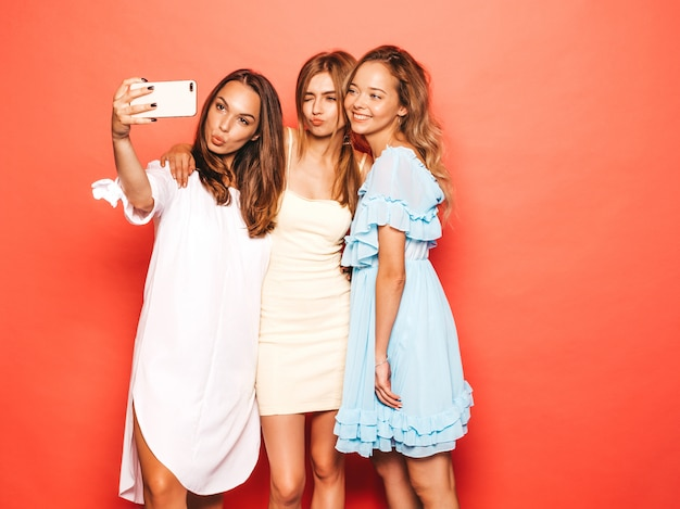 トレンディな夏服で3人の若い美しい笑顔流行に敏感な女の子。ピンクの壁に近いポーズセクシーな屈託のない女性。ポジティブなモデルが夢中になります。スマートフォンでセルフポートレート写真を撮る