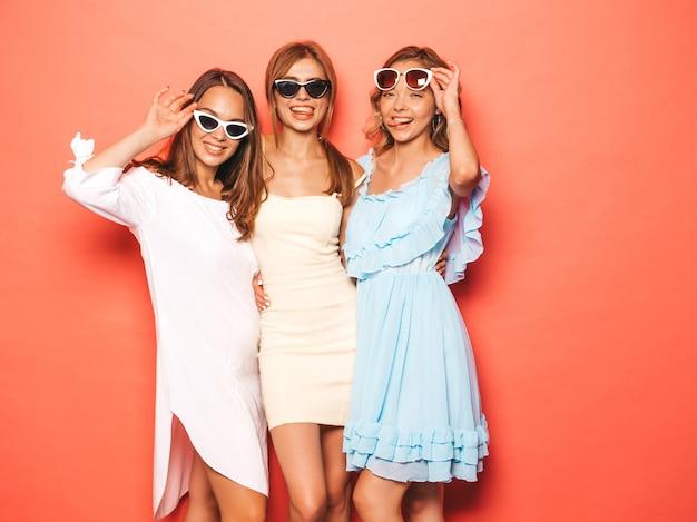 トレンディな夏服で3人の若い美しい笑顔流行に敏感な女の子。ピンクの壁に近いポーズセクシーな屈託のない女性。ポジティブなモデルが夢中になって楽しんでいます。サングラスで