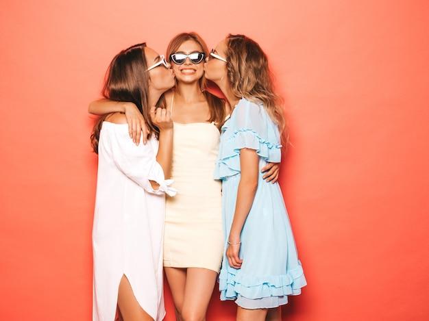 トレンディな夏服で3人の若い美しい笑顔流行に敏感な女の子。ピンクの壁に近いポーズセクシーな屈託のない女性。クレイジーになって楽しんでいるポジティブなモデル。