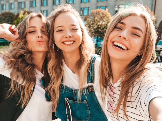 夏服で3人の若い笑顔ヒップスター女性。スマートフォンでセルフポートレート写真を撮る女の子。通りでポーズをとるモデル。肯定的な顔の感情を示す女性