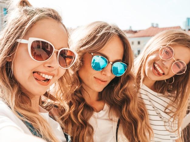 夏服で3人の若い笑顔の流行に敏感な女性。スマートフォンでセルフポートレート写真を撮る女の子。通りでポーズをとるモデル。サングラスで肯定的な顔の感情を示す女性