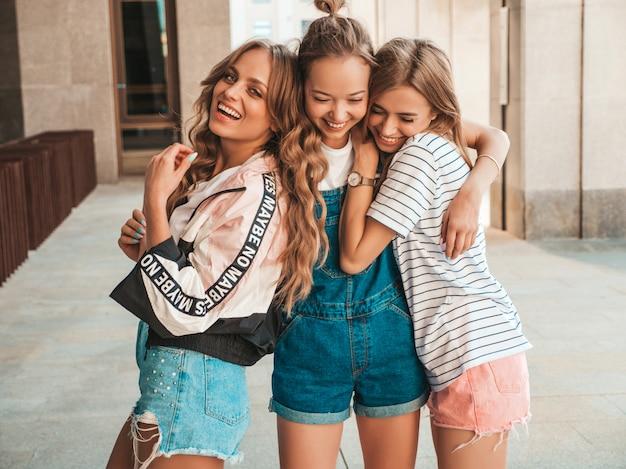 トレンディな夏服の3人の若い美しい笑顔流行に敏感な女の子の肖像画。セクシーな屈託のない女性が路上でポーズします。