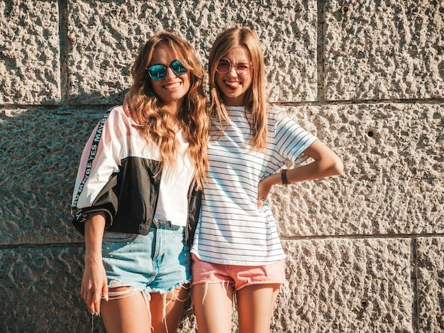 トレンディな夏服の3人の若い美しい笑顔流行に敏感な女の子の肖像画。通りの壁の近くでポーズセクシーな屈託のない女性。サングラスで楽しんでいる肯定的なモデル