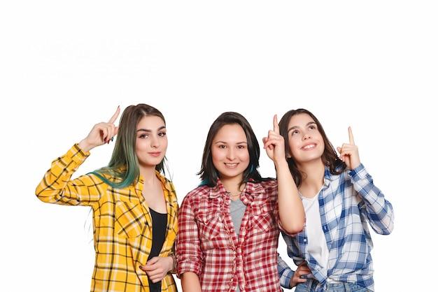 3人の美しい少女が人差し指を頭の上に向けます。