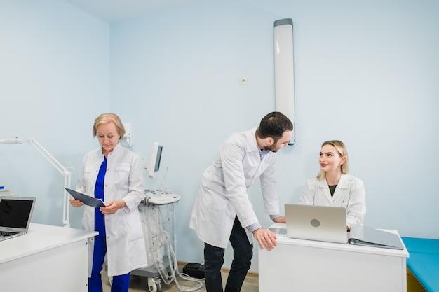 3人の医師が一緒にオフィスで会議をしながら新しい治療法について話し合う写真。ラップトップコンピューターを使用して、新しい治療方法について話し合う医師。