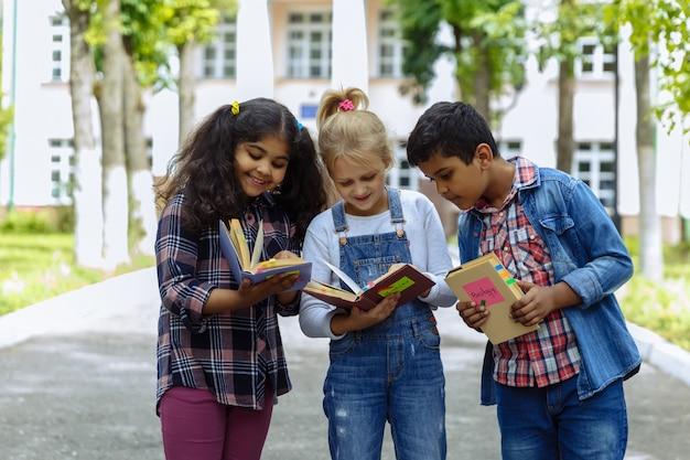 学校に戻る。学校の前でバックパックを抱きしめて笑っている3人の友人を閉じます。校庭で楽しんでいる学校の子供たちの混合人種グループ。