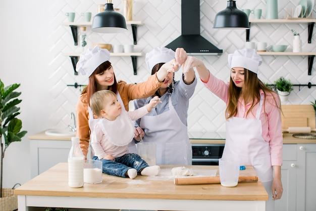 白いエプロンを着た3世代の女性が母の日にキッチンでピザ生地を作っています
