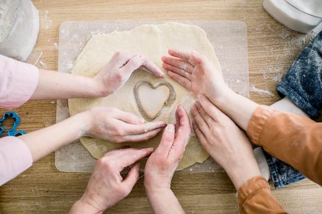 料理と家庭のコンセプト-自宅で新鮮な生地からクッキーを作る女性の手のクローズアップ。 3人の女性の手がハートの形でクッキーを保持