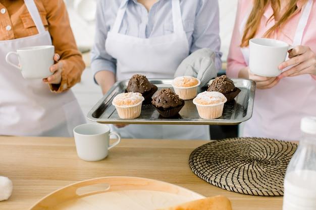 カップケーキ、マフィン、一緒に焼く-3人の女性が、焼きたてのチョコレートとバニラのカップケーキをベーキングトレイに入れます。家族の料理、母の日のコンセプト