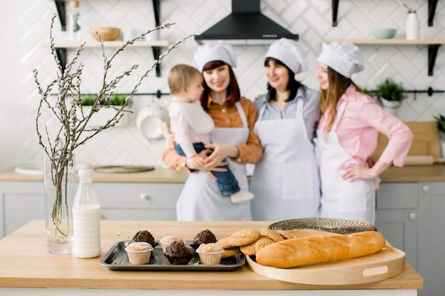 3世代の女性がキッチンで料理をしていて、マフィンとクッキーのあるテーブルに焦点を当てています。自家製料理と小さなヘルパー。幸せな家族。キッチンで焼く。イースター休暇や母の日