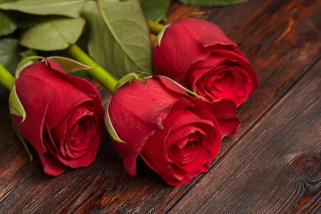 木製のテーブルに3つの美しい赤いバラ