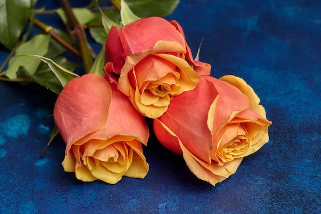 青い表面に3つの美しいオレンジ色のバラ