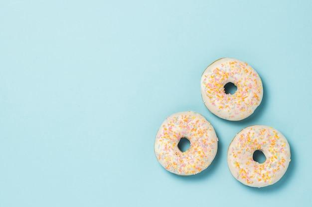 青色の背景に3つの新鮮なおいしい甘いドーナツ。ファーストフードのコンセプト、ベーカリー、朝食、。ミニマリズム。フラット横たわっていた、トップビュー。
