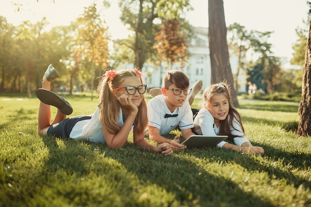 笑顔の学齢期の友達3人が芝生に寝転んでいます。子供の手にタブレット