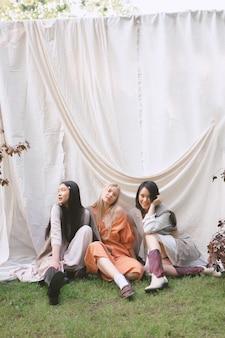 地面に座って、庭で笑顔の3人の美しい女性。