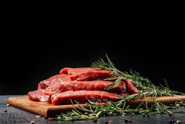 黒い壁にローズマリーとまな板の上の3つの生の牛肉ステーキ。