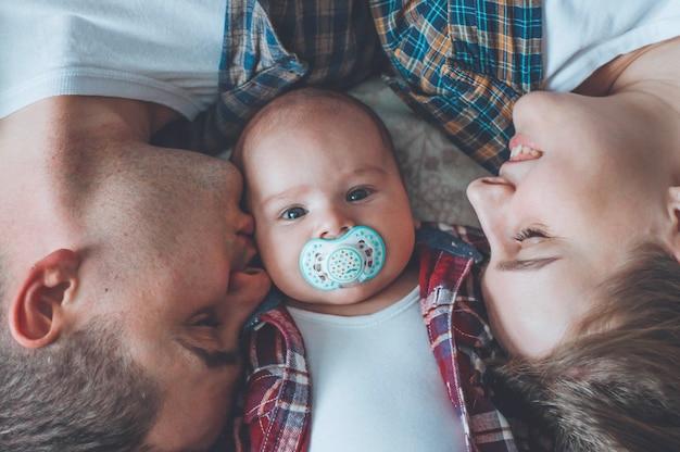 生後3か月の息子を持つ父と母の肖像画。幼い息子にキス。幸せな若い家族。家族での検疫
