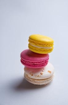 3つのおいしいマカロンと灰色の背景にピンク、白、黄色のスタック