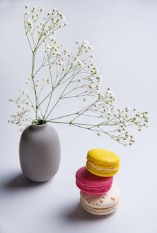 3つのおいしいマカロンとピンク、白、黄色のスタックと灰色の背景に花の花瓶。