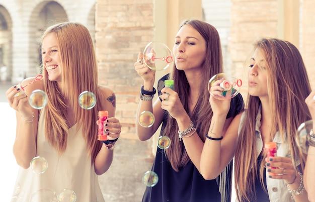 シャボン玉を作る3つの若い女性