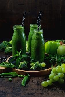 中央の木製の壁の上と、緑の野菜と果物の周りに、野菜と果物から作られた最も有用な緑のスムージーの3つのボトルが立っています。縦の写真。上面図。