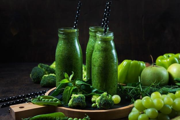 中央の木製の壁の上と、緑の野菜と果物の周りに、野菜と果物から作られた最も有用な緑のスムージーの3つのボトルが立っています。横の写真。