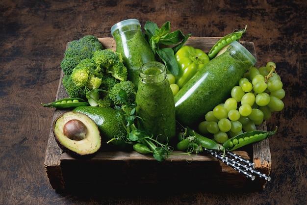 野菜と果物から作られた最も健康的な緑のスムージーのボトル3本が、木製の箱の中にあり、緑の野菜と果物の周りにあります。横の写真。